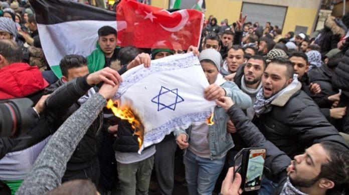 Moslems zünden in Berlin eine Israel-Flagge an.