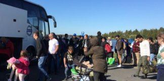 """""""Flüchtlinge"""" besteigen im schwedischen Haparandaeinen Bus, der sie in ein Aufnahmezentrum bringen soll"""