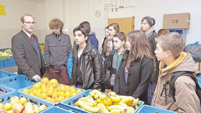 Oliver Witte (links) gibt Schülern eines Remscheider Gymnasiums einen Einblick in die Arbeit der Tafel.